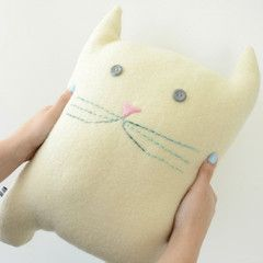 This large, cream cat is sewn from vintage wool, and felt. This hipster cat cushion has a sweet little hand-sewn face and just wants to save the world - he has a peace sign on his back. $49.00