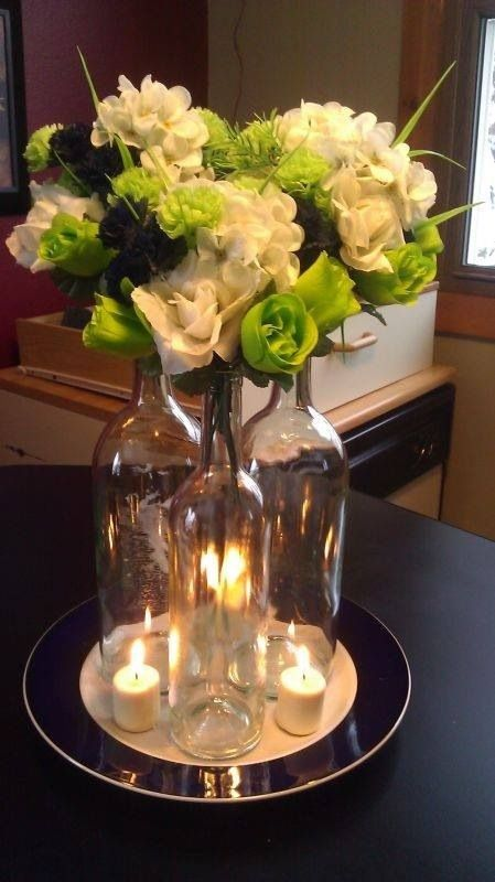 Wine bottle flower arrangement wedding pinterest for Wedding table decorations with wine bottles