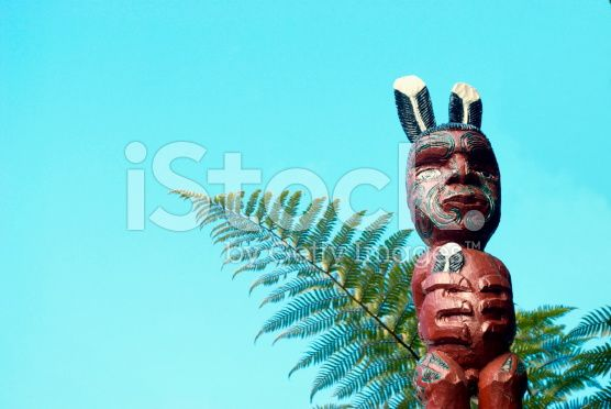 Maori Pou Figure with Ponga Fern and Sky royalty-free stock photo