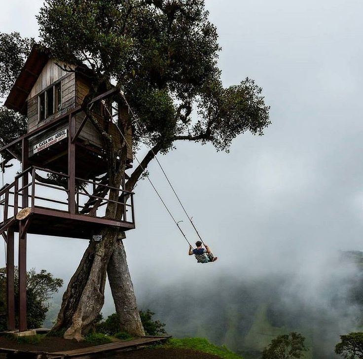 Swinging off the edge of the world at Casa del Arbol in Bańos, Ecuador. The swing's unique location 2,600 m above sea level offers visitors a beautiful view of the Tungurahua Volcano.