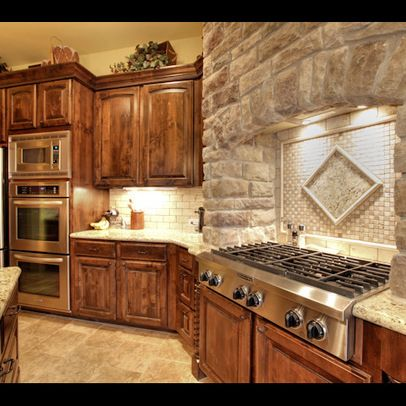stone work above the grill and backsplash, knotty alder cabinets