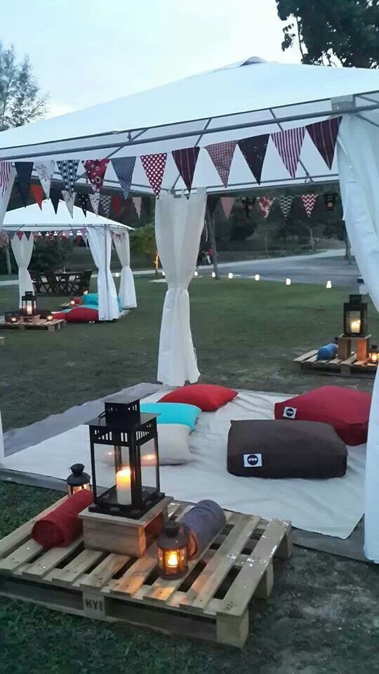 Chillout look of a Gazebo party area: cushions bean bags and pallet used as tables, white Gazebos, pallets, lanterns and scatter cushions.