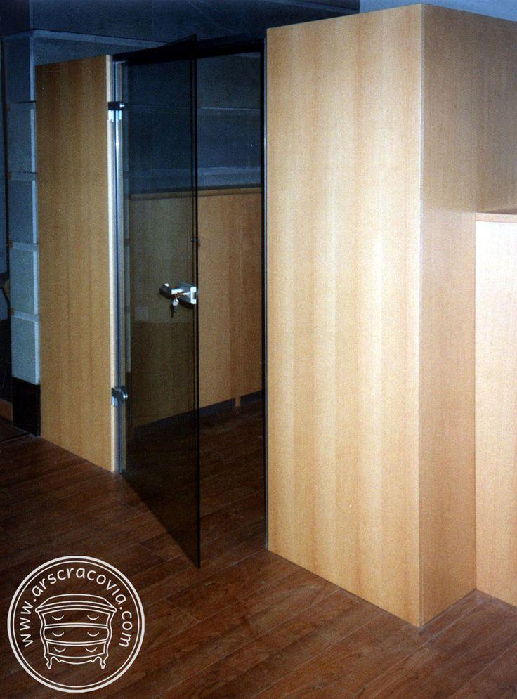 Pomieszczenie ze szklanymi drzwiami wydzielone z otwartej przestrzeni biurowej ściankami z szaf.
