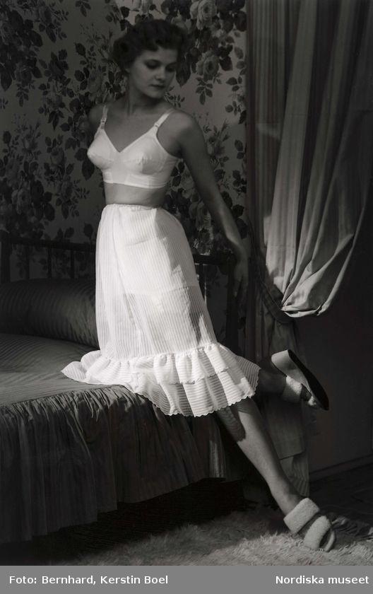 Modell i underkläder från Twilfit. Vit BH och vit underkjol med volang, tofflor. Står med ena benet på en säng. Matta, draperi och blommig tapet i bakgrunden. Foto: Kerstin Bernhard, 1954
