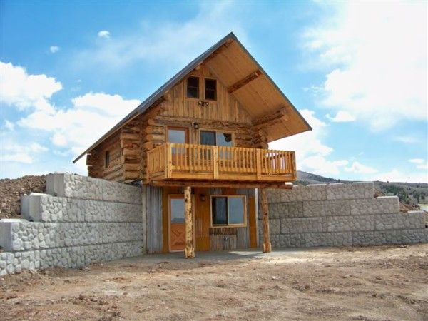 """Tiny house with basement in hillside. The recently completed this 16x22 designed by the client and built to his specification. The cabin was set on full daylight or """"wall-out"""" basement."""