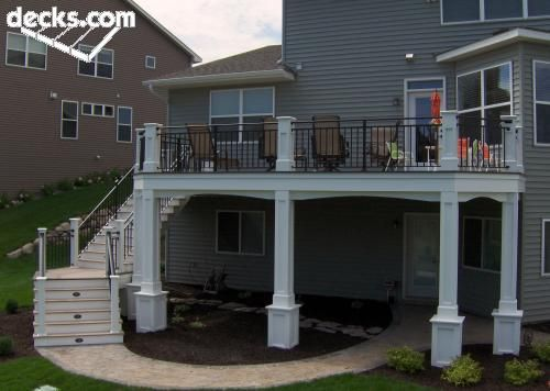second story deck with curved around stairs, with in stairs lighting, white columns and small patio underneath