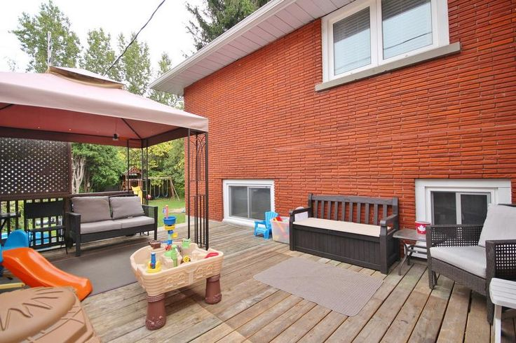 Backyard deck with seating and children's play area.