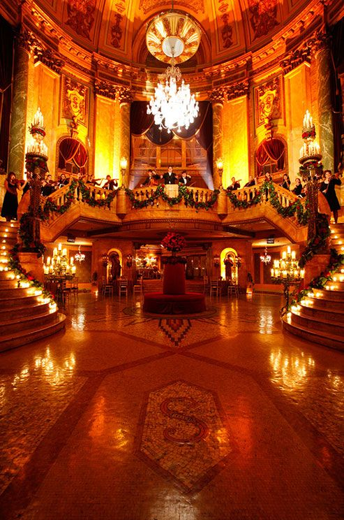 Votive candles line a double grand staircase while up-lighting frames an orchestra conductor and two bassists.