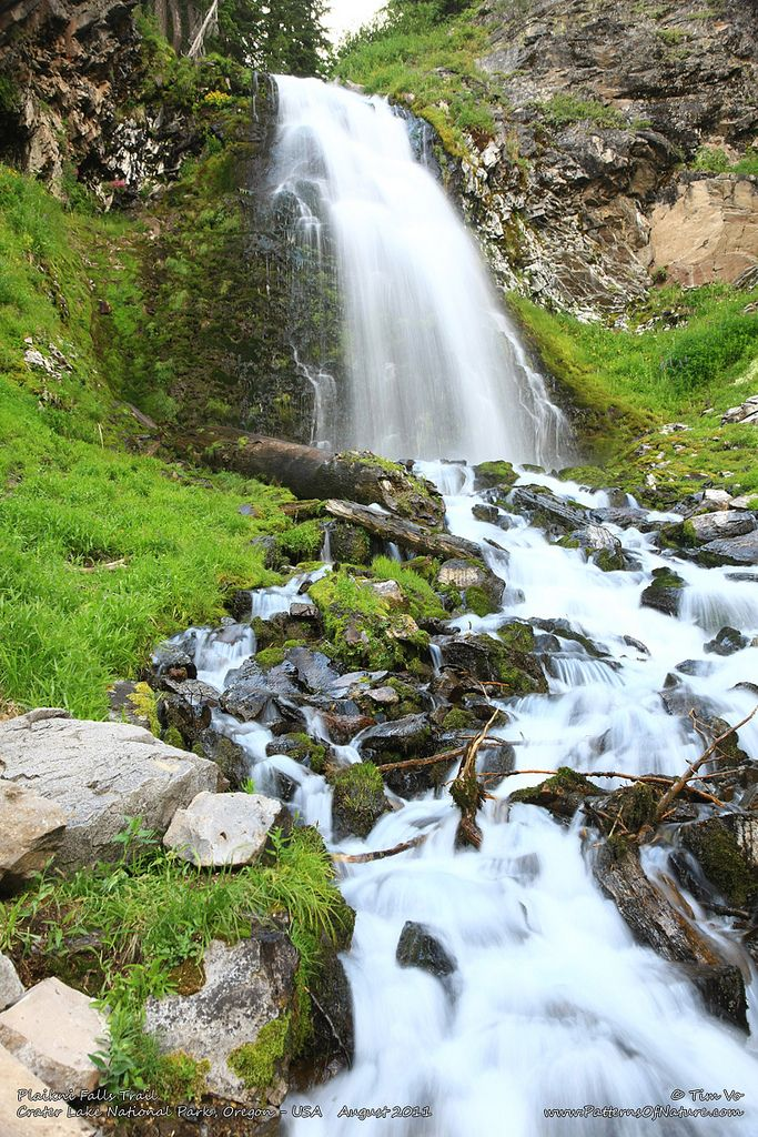 The waterfall cascades ethereally over a mossy rock wall and pours into the lovely Sand Creek.