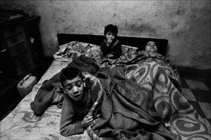 Letizia Battaglia | La donna ed i suoi bambini stanno sempre a letto. In casa non ci sono né luce né acqua, Palermo, 1978