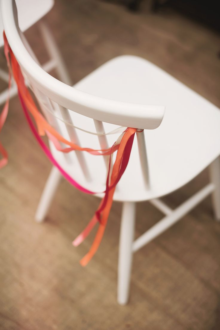 White chairs and colorful ribbons by GRUNT STUDIO