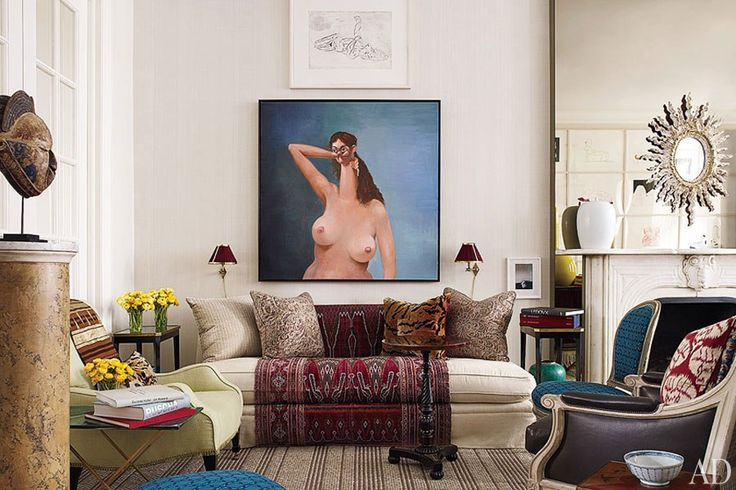 Beside the living room's mirrored chimney breast hangs a George Condo nude; an 18th-century Persian panel drapes the sofa.