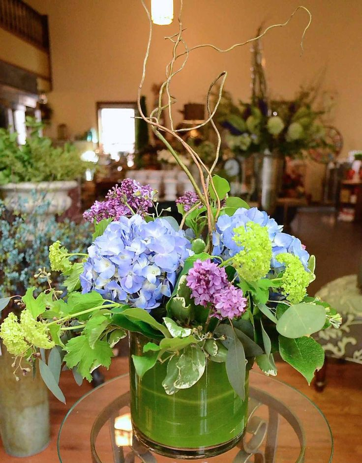 "6"" cylinder blue hydrangea, lilac, viburnum, willow, greens"