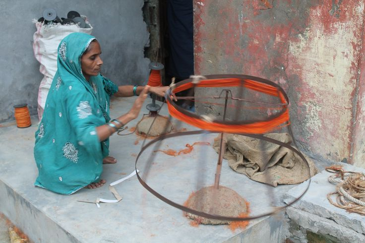 "Women in villages are spinning yarn on a charkha/spinning wheel. The yarn will eventually be used for weaving a floor covering for ""HANDMADE WORLD"""
