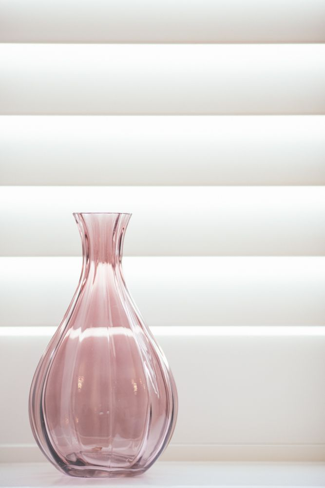 Blush vase against the clean lines of a white shutter