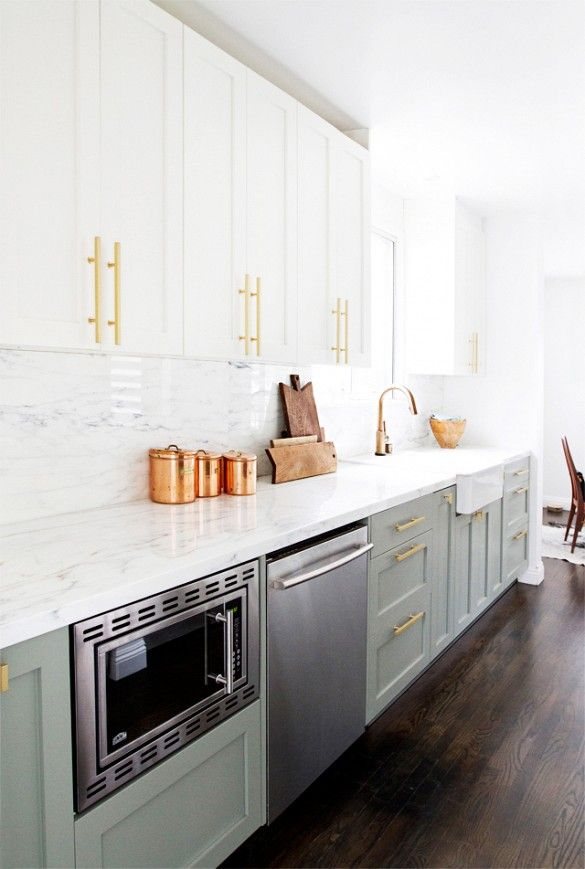 Mint kitchen cabinets with white marble backsplash and brass and copper accents.
