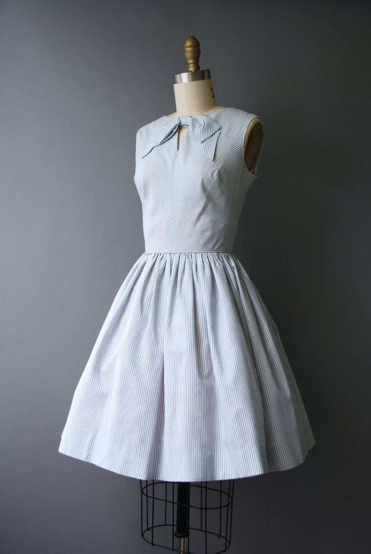 Adorable 1960s Bobbie Brooks dress with fitted, sleeveless bodice, full skirt, blue and white pinstripes, keyhole bodice and a large, decorative