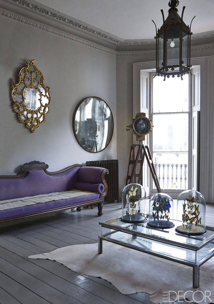 An 18th-century Rococo-style English mirror and a 20th-century convex mirror hang above an Irish Regency sofa; the cocktail table is 20th century, and a ship's searchlight from the 1900s is mounted on a military tripod base; the walls are painted in Elephant's Breath and the floors in Charleston Gray, both from Farrow & Ball.