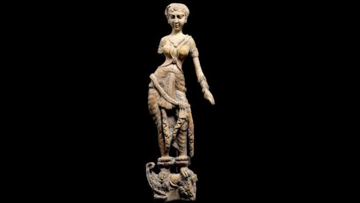 STATUETTE OF A WOMAN STANDING ON A MAKARA, BEGRAM. IVORY. 1ST–2ND CENTURIES AD This statuette once decorated a piece of wooden furniture that turned to dust. The woman may represent the Indian river goddess Ganga, whose mount is the mythological makara, a creature that is part crocodile, part elephant, and part fish.