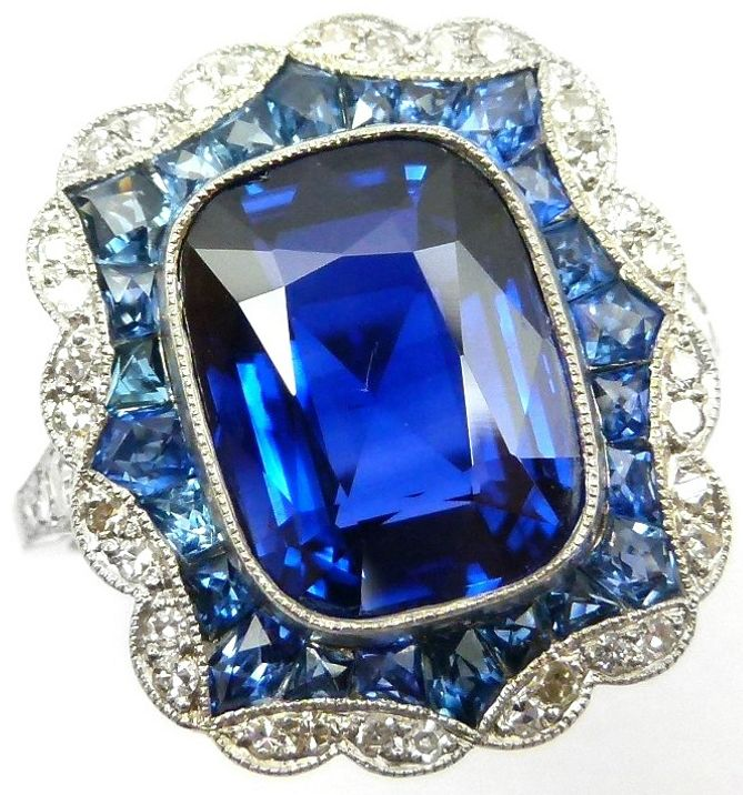Art Deco sapphire and diamond ring with a 5.33 carat Burma sapphire, an oblong two-row border of calibre cut sapphires and diamonds with a scalloped edge, and diamond line shoulders. Via Diamonds in the Library.