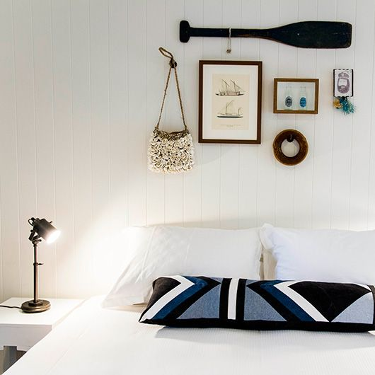 vintage collectibles above a white bed at the albatross inn / sfgirlbybay