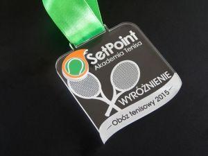 Medal z ciekawym motywem rakiet do tenisa -SetPoint Akademia Tenisa. Medal z pleksi przezroczystej grawerowanej i kolorowego laminatu.