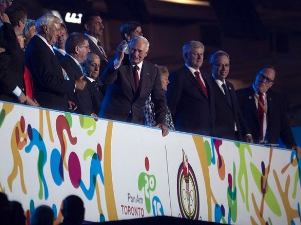 Governor General David Johnston salutes the crowd alongside TO2015 Chairman David Peterson, left, and Canadian Prime Minister Stephen Harper, right.