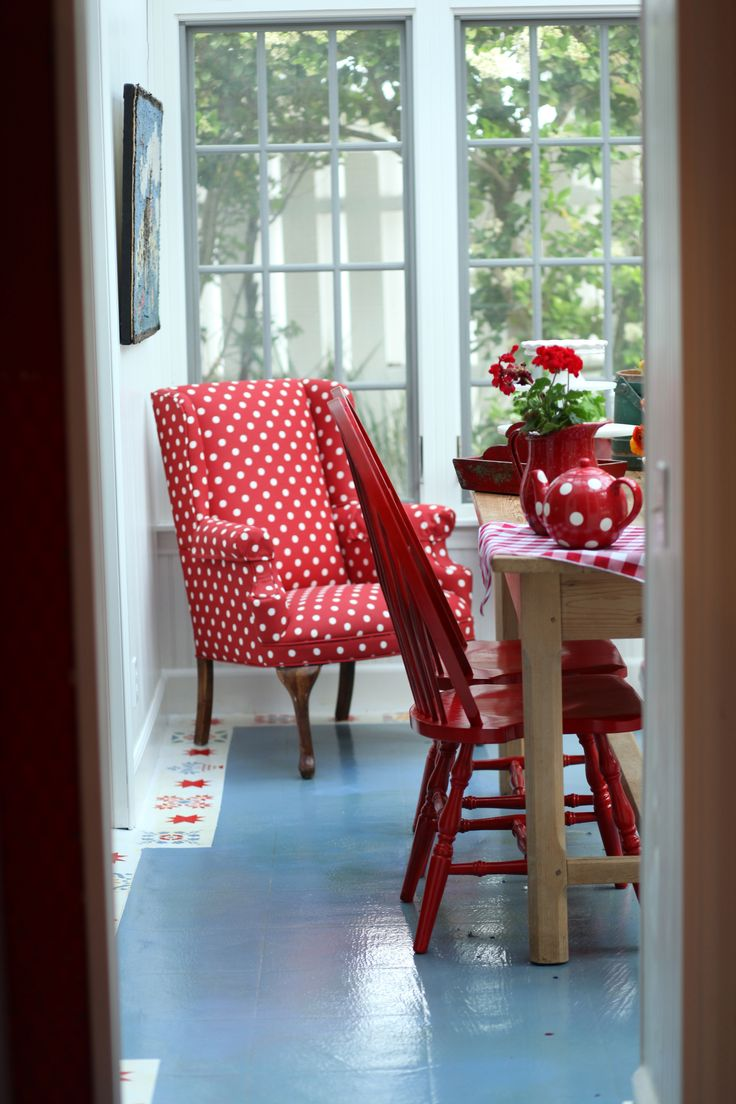 Red polka dot chair, solid red dining chair, blue floor.                                                                                                                                                      More