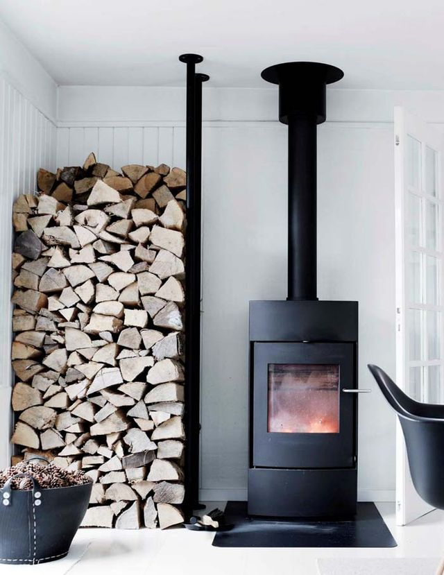 A Scandinavian Farmhouse In Black & White. Now that's a good looking wood burning stove and a serious log pile!