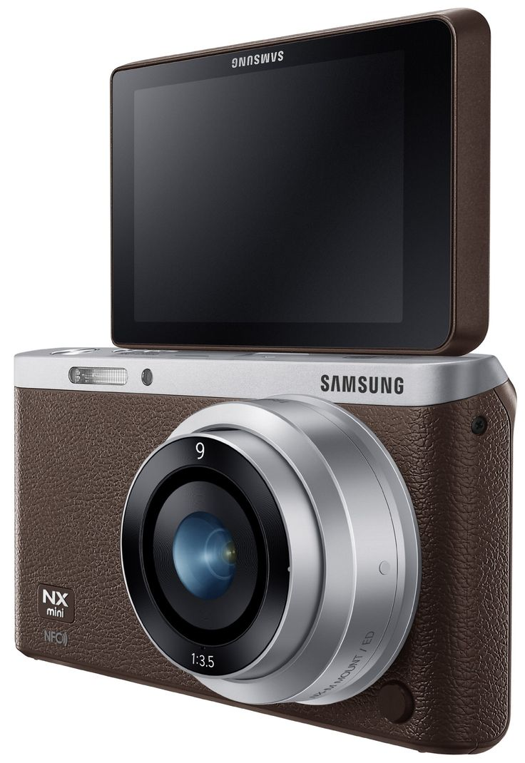 """Samsung NX Mini 20.5MP CMOS Smart WiFi & NFC Mirrorless Digital Camera with 9mm Lens and 3"""" Flip Up LCD Touch Screen (Brown). 20.5MP BSI CMOS Sensor for high-quality images and life like colors with crystal clear resolution. Stylishly slim (22.5mm), & impressively light (158g). Share your best photos instantly with Family and Friends with Built-in Wi-Fi with NFC. SMART features - Social Media Upload, E-mail, Photo beam, DirectLink, MobileLink, PC Auto-backup, Remote Viewfinder PRO…"""