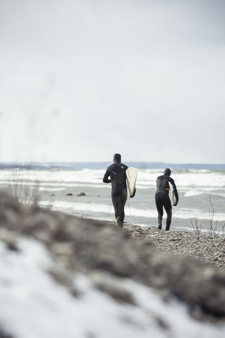 Two surfers, about to hit the icy water and surf their guts out.