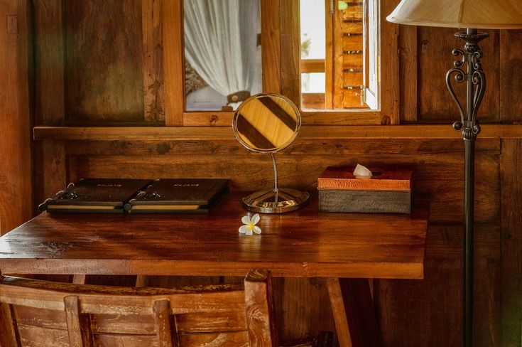 A mirror reflecting light and shadow atop a lovely, simple wooden desk at Kajane Mua, Bali.