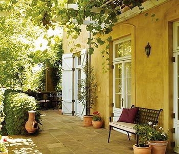 Picture a Mediterranean courtyard and you're likely to imagine ochre walls, a vine-covered pergola and lots of terracotta. Add shots of colour from geraniums and glazed pots, and you've got an intimate outdoor entertaining space.