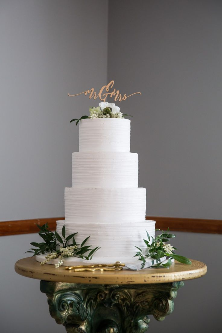 White Wedding Cake Decorated with Greenery & Lasercut Topper