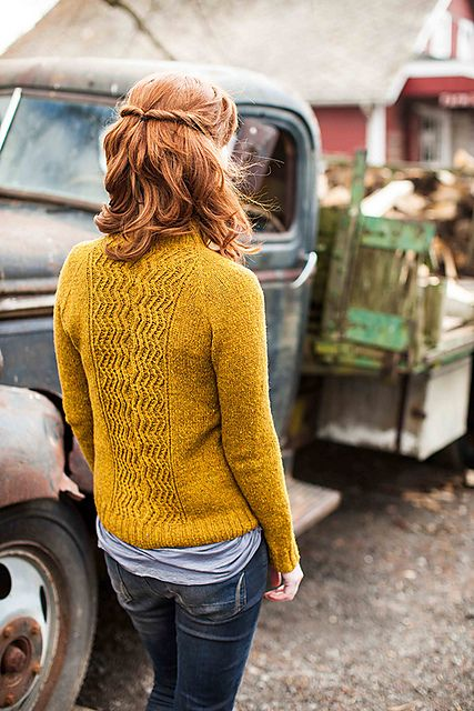 Mustard yellow knit sweater, light blue jersey undershirt and dark washed lightly distressed denim.