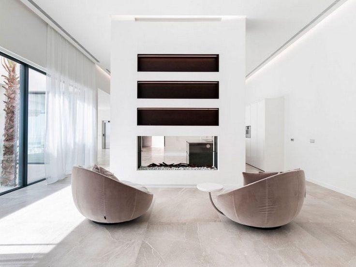 carrelage grand format en gris, fauteuils en velours, cheminée moderne avec foyer fermé et rideaux blancs