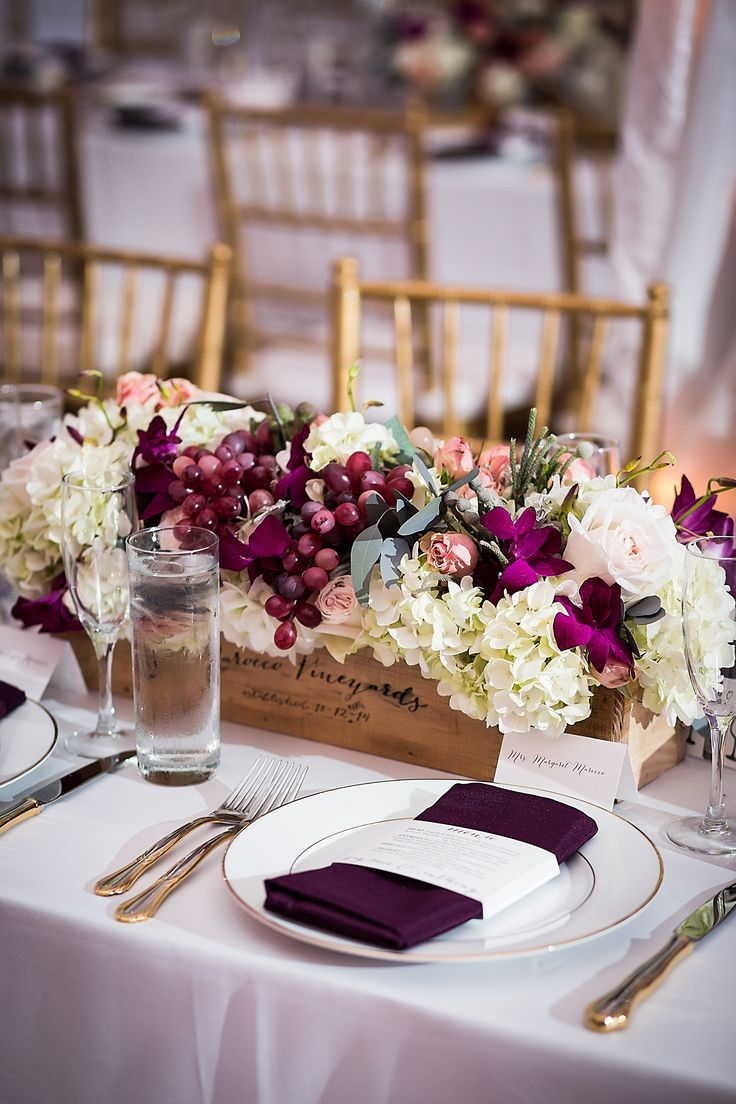Wine-themed centerpieces at the reception were made up of grapes, fuchsia orchids, white hydrangeas, blush roses and eucalyptus leaves arranged in wine boxes.