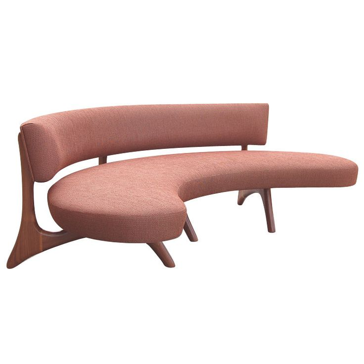 A biomorphic walnut sofa with curved backrest and a floating platform seat set on sculptural carved legs which blend seamlessly into the support for the back.  A reproduction of the amazing design of Vladimir Kagan.