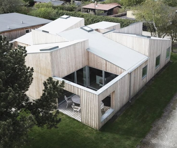 The Roof House by Sigurd Larsen | Sigurd Larsen's Roof House features intersecting slanted roofs | wood cladding
