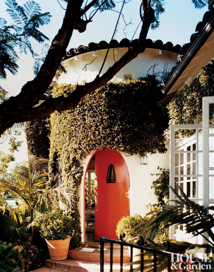 An oversize mandarin-hued door opens into a West Hollywood home.