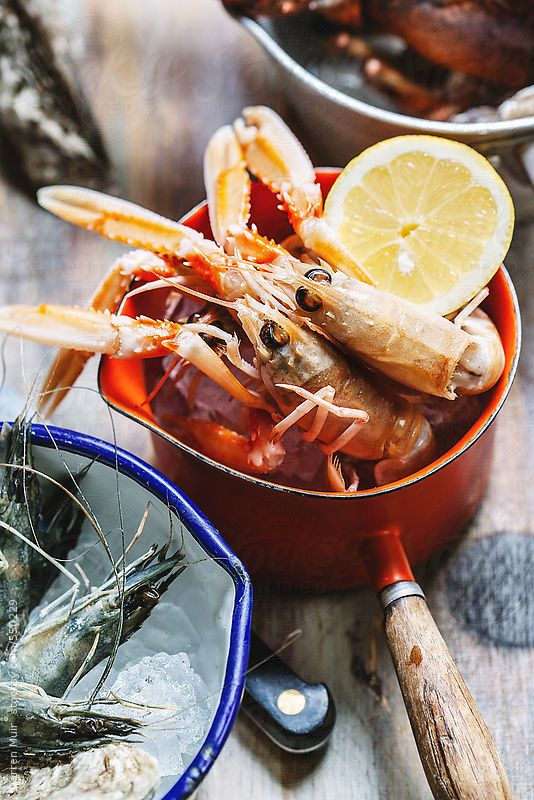 Langoustine and other shelled seafood in pots on a wooden surface with focus on the langoustine. by Darren Muir for Stocksy United