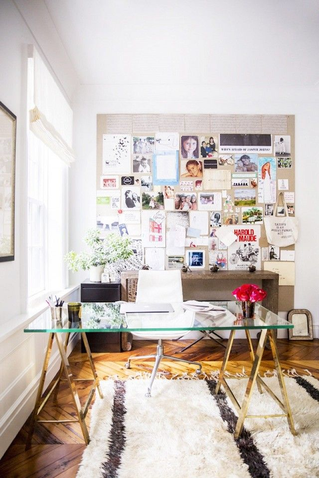 Chic office space with a gold and glass desk, fresh flowers, and a large inspiration board