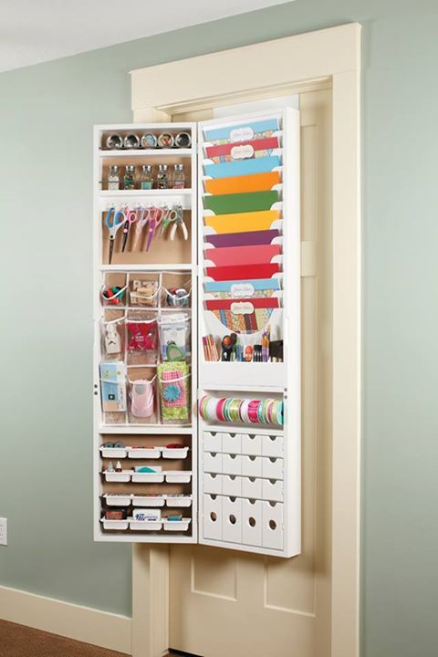 "The Over-The-Door Craft Armoire from Jinger Adams has a cork front, closing magnetic door and can also be mounted to a wall. Other features include: Four drawers and four craft trays Six large and three small clear pockets Five paintbrush and/or pen holders Eleven 12"" x 12"" paper trays and one ribbon rod Six scissor hooks Two storage shelves"