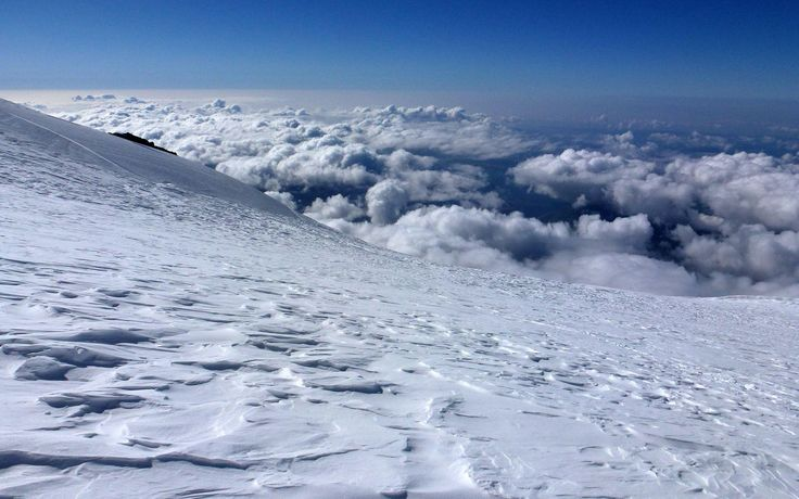 awesome snowy mountain peak above the clouds