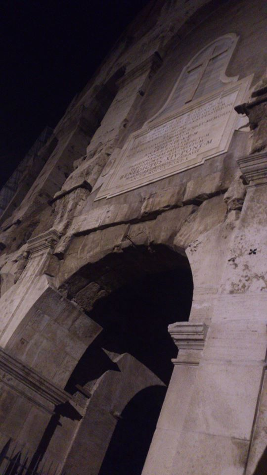 This is one of the old archs leading into the Colosseum. Above it a Christian decoration, a cross and a pope mention