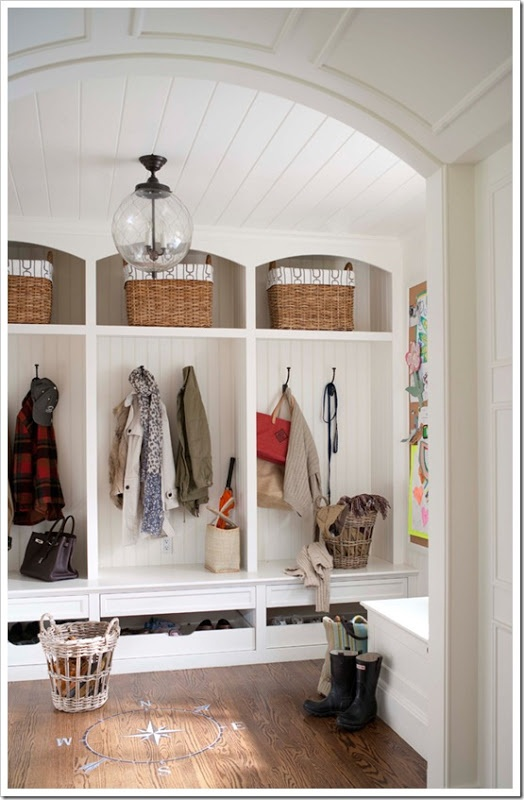 A white mudroom designed with large cubbies and wood floors & ceiling