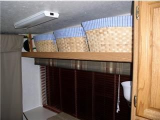 You always need storage in a trailer. Put a shelf above the bedroom window and use baskets for more storage.