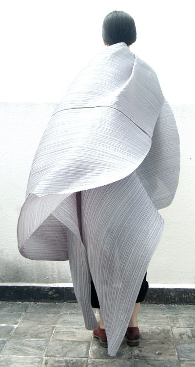 In the 1980s, Issey Miyake began to experiment with new methods of pleating that  allow both flexibility of movement as well as ease of care and production. This  resulted in a new technique called garment pleating in 1993's Pleats Please in which the garments are cut and sewn first, then sandwiched between layers of paper and fed into a heat press, where they are pleated. The fabric's 'memory' holds the pleats and when the garments are liberated from their paper cocoon, they are ready-to…