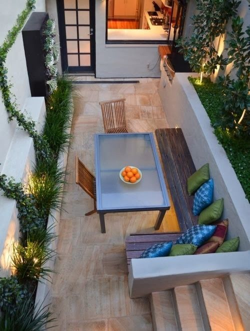 This small court yard has been made to feel very welcoming with the use of concrete and hard surfaces. I think the warm lighting helps. I really like the retaining borders.: