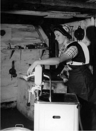 Afbeelding van een jonge vrouw in klederdracht in de bijkeuken van een huis te Eemdijk (gemeente Bunschoten), bezig met het mangelen van wasgoed bij de wasmachine. 1958 Heemskerck Düker, W.F. van (fotograaf) #Utrecht #Spakenburg